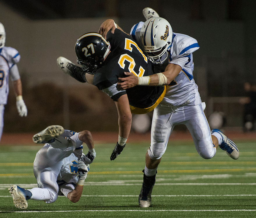 Foothill's Robby Forkey is upended by Fountain Valley's Jacob Church on a carry during Friday's game at Tustin High School
