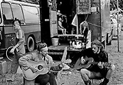 Two men sit playing guitars in front of van, where a child sits looking out of. Glastonbury 1994