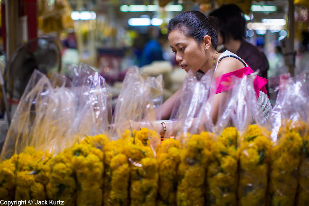 19 OCTOBER 2012 - BANGKOK, THAILAND:   A vendor reads her newspaper in the Bangkok Flower Market. The Bangkok Flower Market (Pak Klong Talad) is the biggest wholesale and retail fresh flower market in Bangkok.  The market is busiest between 3:30AM and 6AM. Thais grow and use a lot of flowers. Some, like marigolds and lotus, are used for religious purposes. Others are purely ornamental.         PHOTO BY JACK KURTZ
