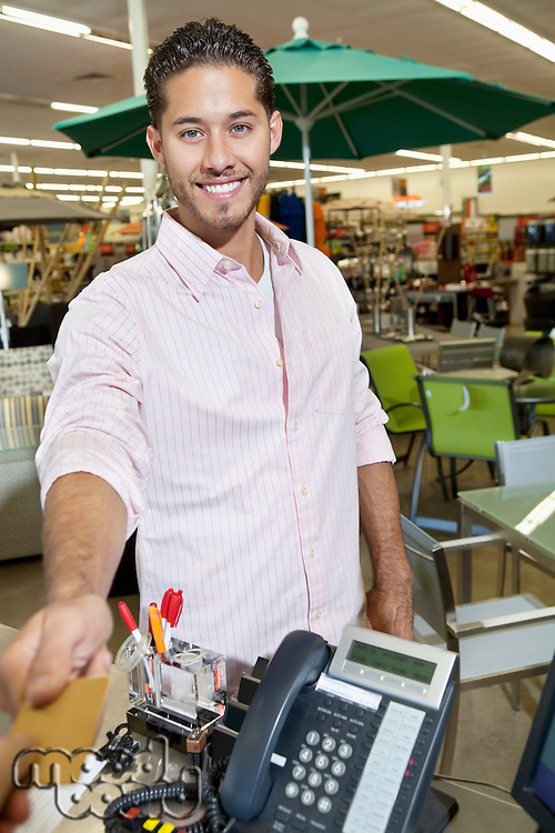Portrait of a happy young man paying through credit card