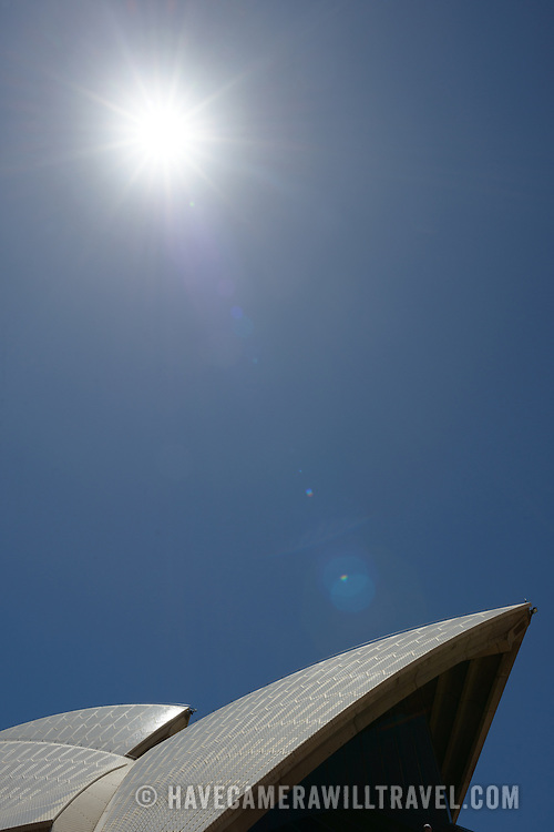 The roof of the Sydney Opera House against a clear blue sky and with the summer sun in the top of the frame.