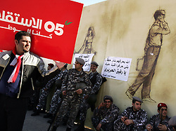 """A demonstrator, with a sign that reads """"Independence 05,"""" stands outside the grave of former Prime Minister Rafik Hariri, while the Lebanese military stand guard, Beirut, Lebanon, Feb. 21, 2005. Several thousand Lebanese gathered at the scene of the bombing that killed Hariri. The crowd demanded a Syrian pullout and an international probe into the assassination."""