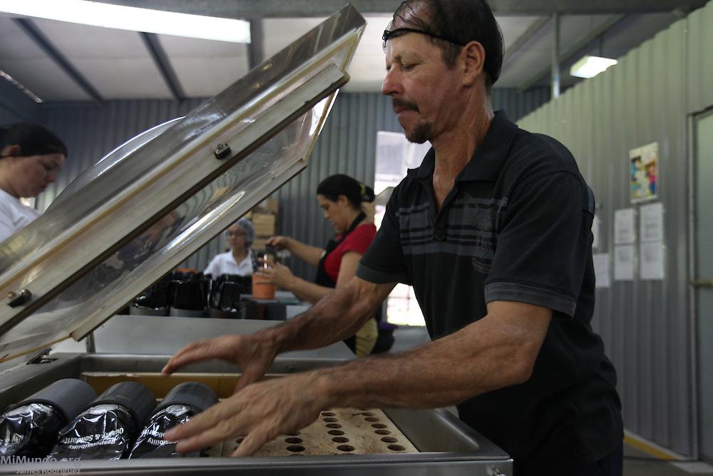 Tranquilo Eladio López packs ground coffee. COOCAFE, Tilarán, Guanacaste, Costa Rica. August 22, 2012.