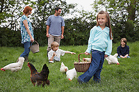 Parents and three children (5-9) with hens in garden