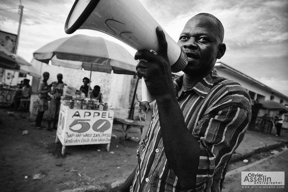 Volunteer Napoleon Mukengue uses a megaphone to announce the upcoming polio vaccination campaign to the population as he walks down a street in Pointe-Noire, Republic of Congo on Thursday December 2, 2010.