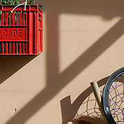 Exterior shadow detail with milk crate planter and chair made from a reused tyre.
