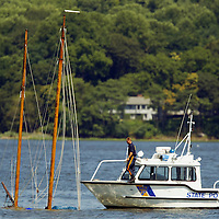 (PPAGE1) Middletown 7/16/2002  A New Jersey State Marine Police boat appoaches the sunken sailboat that was involved in a jet ski accident late last night that resulted in a fatality.   Michael J. Treola Staff Photographer......MJT