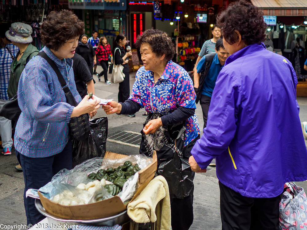 14 JUNE 2018 - SEOUL, SOUTH KOREA: A woman sells songpyeon stuffed with mugwort in Namdaemun Market. Songpyeon is a rice treat made with short grained rice. Namdaemun Market is one of the oldest continually running markets in South Korea, and one of the largest retail markets in Seoul. The streets in which the market is located were built in a time when cars were not prevalent, so the market itself is not accessible by car. The main methods of transporting goods into and out of the market are by motorcycle and hand-drawn carts. It occupies many city blocks, which are blocked off from most car traffic due to the prevalence of parking congestion in the area.       PHOTO BY JACK KURTZ