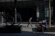 Businessmen sits next to a City of London sculpture entitled Southern Shade by Nigel Hall.