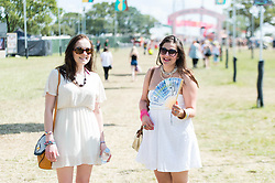 © Licensed to London News Pictures. 13/06/2014. Isle of Wight, UK.   Girls in white summery dresses, with one cooling herself with a fan, enjoy the hot sunny morning weather at Isle of Wight Festival 2014.   The Isle of Wight festival is an annual music festival that takes place on the Isle of Wight. Photo credit : Richard Isaac/LNP