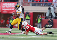November 25, 2011: Iowa Hawkeyes running back Marcus Coker (34) tries to pull away from Nebraska Cornhuskers safety Austin Cassidy (8) on a run during the second half of the NCAA football game between the Iowa Hawkeyes and the Nebraska Cornhuskers at Memorial Stadium in Lincoln, Nebraska on Friday, November 25, 2011. Nebraska defeated Iowa 20-7.