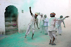 Men celebrating holy in a courtyard. Photo taken while traveling in Rajasthan, India, with Steve McCurry.