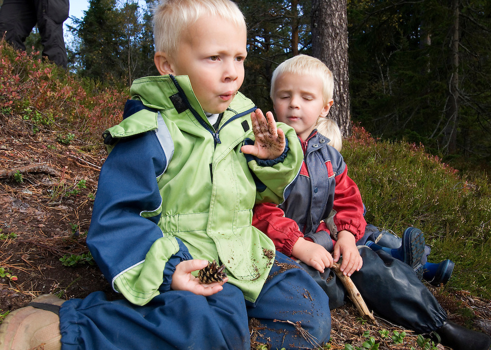Boy in a Norwegian naturbarnehage (nature nursery) with dirty hands and a pine cone