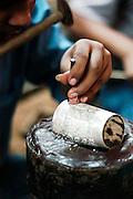 India, New Delhi, Majnu Ka Tila tibetan refugee camp. Silversmith ornamenting a wrist band with a hammer and nail