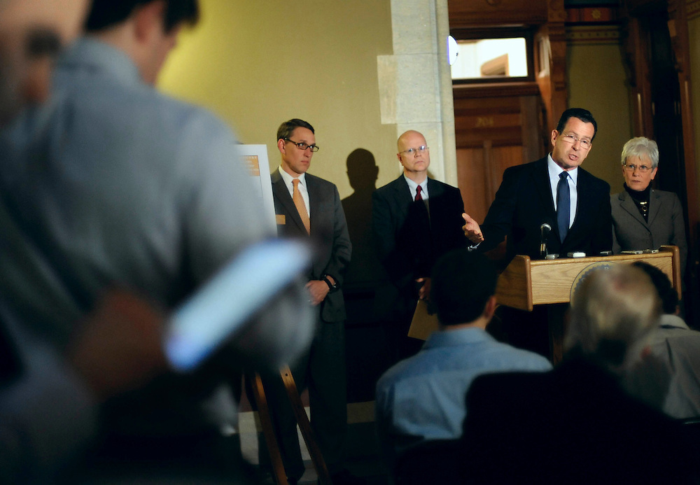 Gov. Dannel P. Malloy, at podium, speaks to the media at the Capitol as budget chief Ben Barnes, left,  state Comptroller Kevin Lembo, second from left, and Lt. Gov. Nancy Wyman, right, look on in Hartford, Conn., Monday, Jan. 23, 2012. Malloy proposed a 20-year plan that will speed up state payments to Connecticut's underfunded state employee pension system. The state's pension fund is currently funded at less than 48 percent, ranking it among the worst in the nation. (AP Photo/Jessica Hill)