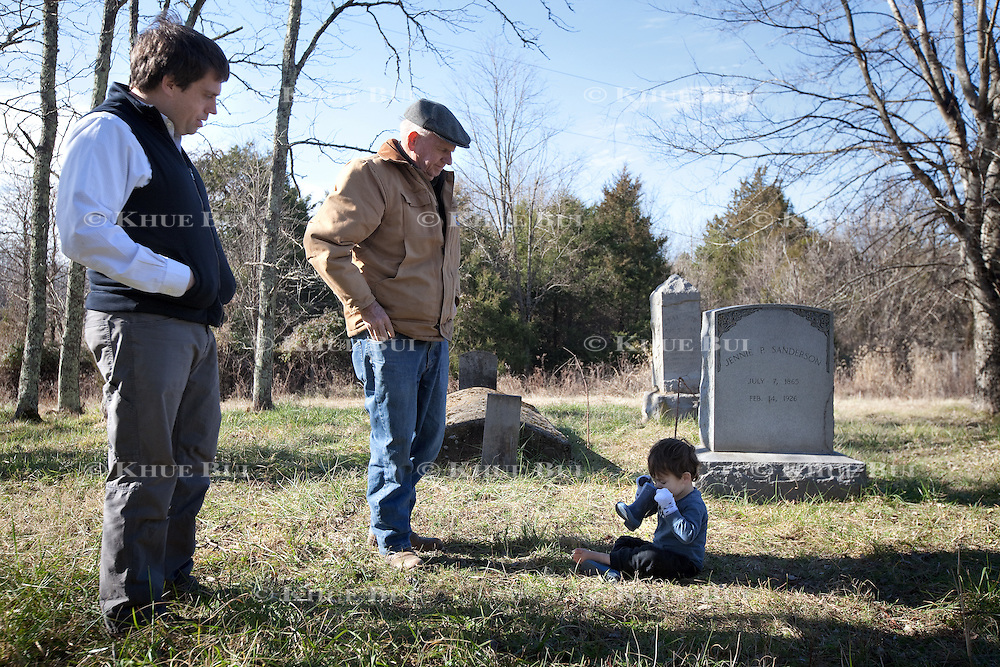 John W. Sanderson (age 75, brown coat); William I. Sanderson &ndash; goes by Bill (age 40, blue fleece vest), son of John W. Sanderson; look on as Luke Pollard Sanderson (age 2), blue and brown vest), son of Bill, grandson of John W. Sanderson; smells his boot during a visit to the private family cemetery Thursday, December 22, 2016, in Cartersville, VA.  The private cemetery contains 4 named graves, but the family believes there are more family members buried here as there are more stones next to the named grave sites.<br /> <br /> Photo by Khue Bui for the New York Times