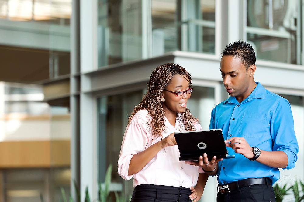 Photo of office workers looking at tablet in a corporate environment. Photographer captures corporate location photography.