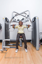 Young woman using the chest press at her local sports leisure centre,