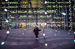 © Licensed to London News Pictures. 14/01/2019. London, UK. A toddler girl runs through a light installation titled Submergance by Squidsoup showing as part of the Canary Wharf Winter Light Festival. Photo credit: Ray Tang/LNP