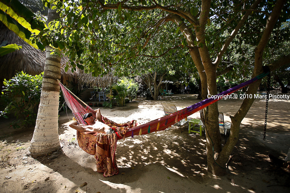 "SHOT 1/20/10 1:16:22 PM - Steve White of Sooke, B.C. relaxes in a hammock at the Junto al Rio in Sayulita, Mexico one afternoon. Sayulita is a small fishing village about 25 miles north of downtown Puerto Vallarta in the state of Nayarit, Mexico, with a population of approximately 4,000. Known for its consistent river mouth surf break, roving surfers ""discovered"" Sayulita in the late 60's with the construction of Mexican Highway 200. In recent years, it has become increasingly popular as a holiday and vacation destination, especially with surfing enthusiasts and American and Canadian tourists. (Photo by Marc Piscotty / © 2009)"