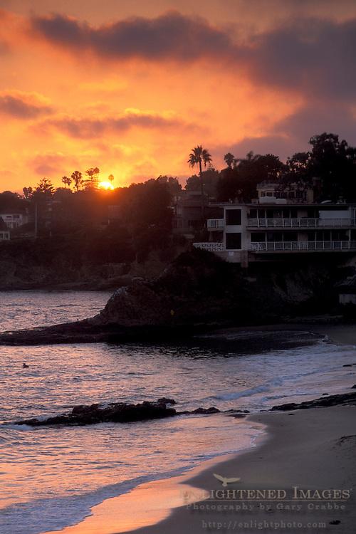 Golden orange sunset over palm trees, apartment, and sandy ocean beach shore, on the coast at Laguna Beach, California