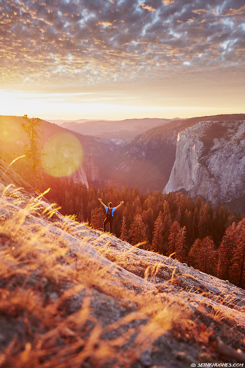 A hiker explores the Sentinel Dome and overlooks the Yosemite Valley with El Capitan in the distance at sunset. Yosemite National Park, California