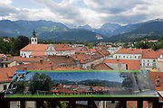 Looking north, an aerial view of the rural town of Kamnik in central Slovenia, on 26th June 2018, in Kamnik, Slovenia. As one of the oldest towns in Slovenia, Kamnik was first mentioned in the 11th century. It was later first mentioned as a town in 1229, at the time when it was an important trading post along the route between Ljubljana and Celje. To the north are the mountain peaks of the Julian Alps that border Slovenia with Austria.