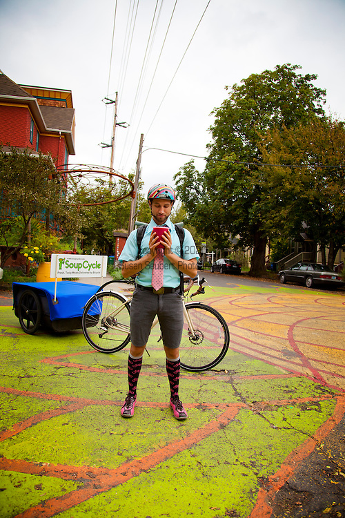 "Jed Lazar, owner of Soupcycle, delivering soup in SE Portland, Oregon.  With a monthly, ""Soupscription,"" subscribers are entitled to one delivery per week which includes a quart of freshly made soup, salad and bread.  Each week Soupcycle makes three kinds of soup - vegan, vegetarian, and meat - that customers may choose from.  He delivers them by a bicycle that has been fitted with a trailer that can carry up to 215 pounds."