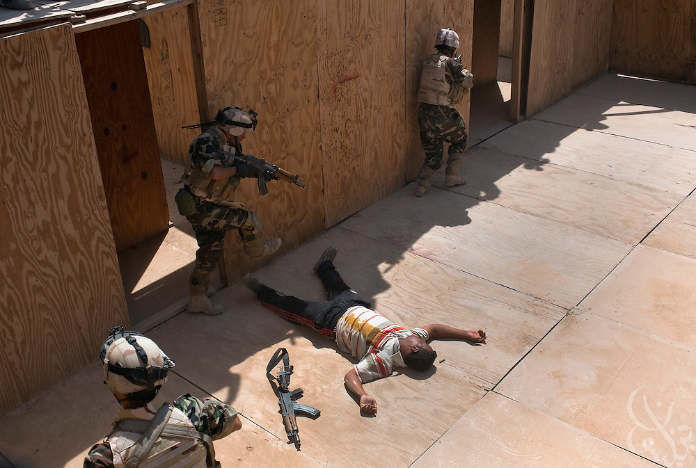 """17th Iraqi Division soldiers pass over a neutralized """"insurgent""""  after simulating shooting him during training exercises August 30, 2010 at the Joint Security Station (JSS) Deason in Mahmoudiyah, Iraq."""