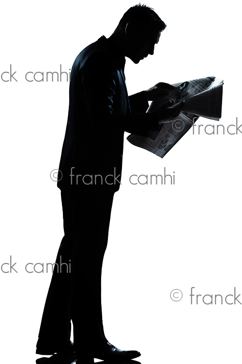 one caucasian man walking reading newspaper  full length silhouette in studio isolated white background