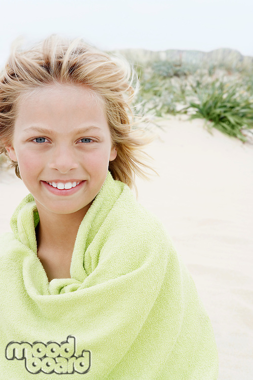 Pre-teen Boy Wrapped in a Towel standing on beach