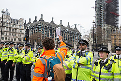 London, UK. 23rd April 2019. A climate change activist from Extinction Rebellion holds up letters to Members of Parliament requesting meetings to discuss the issue of climate change in front of a police cordon in Parliament Square positioned to prevent fellow activists from attempting to deliver such letters.