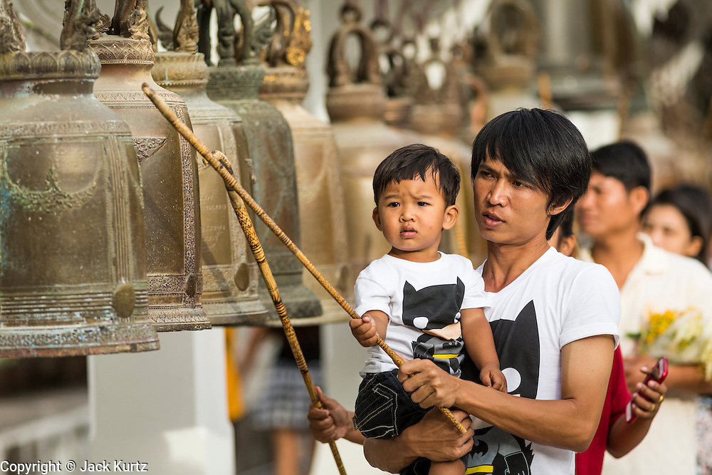 """22 JULY 2013 - PHRA PHUTTHABAT, THAILAND:  People ring prayer bells during the Tak Bat Dok Mai at Wat Phra Phutthabat in Saraburi province of Thailand, Monday, July 22. Wat Phra Phutthabat is famous for the way it marks the beginning of Vassa, the three-month annual retreat observed by Theravada monks and nuns. The temple is highly revered in Thailand because it houses a footstep of the Buddha. On the first day of Vassa (or Buddhist Lent) people come to the temple to """"make merit"""" and present the monks there with dancing lady ginger flowers, which only bloom in the weeks leading up Vassa. They also present monks with candles and wash their feet. During Vassa, monks and nuns remain inside monasteries and temple grounds, devoting their time to intensive meditation and study. Laypeople support the monastic sangha by bringing food, candles and other offerings to temples. Laypeople also often observe Vassa by giving up something, such as smoking or eating meat. For this reason, westerners sometimes call Vassa the """"Buddhist Lent.""""    PHOTO BY JACK KURTZ"""