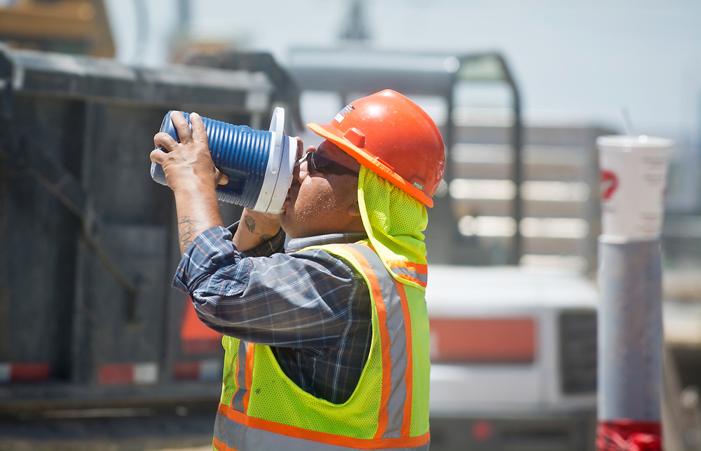 """mkb062017a/metro/Marla Brose --  Manuel Abeita, a road worker on Central Ave. takes a drink while working in about 100 degrees weather, Tuesday, June 20, 2017. """"Stay hydrated,"""" said Abeita about working in the heat.   (Marla Brose/Albuquerque Journal)"""
