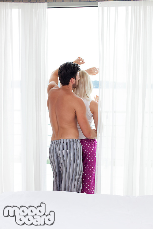 Rear view of young couple looking through window of hotel room