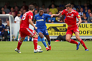 AFC Wimbledon attacker Michael Folivi (17) battles for possession with Accrington Stanley defender Ross Sykes (5) and Accrington Stanley defender Seamus Conneely (28) during the EFL Sky Bet League 1 match between AFC Wimbledon and Accrington Stanley at the Cherry Red Records Stadium, Kingston, England on 17 August 2019.