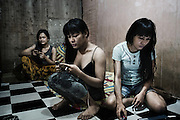 """JAKARTA, INDONESIA, MARCH 2013: Ajurn and her roomates talking to clients through mobile apps. Internet dating is becoming more and more common in the waria community and the profit can be ten times higher than the """"street fee""""."""