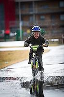 Ari Carl úti að hjóla í polla. Young boy riding his bike into pools of water.