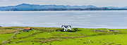 Traditional Scottish farmhouse home and farm on Wester Ross coastal trail near Applecross, in North West Coast of Scotland. Behind is Isle of Raasay and Skye with Cuillin mountains