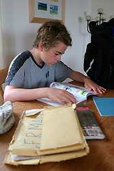 Secondary schoolboy revising or doing his homework at home UK