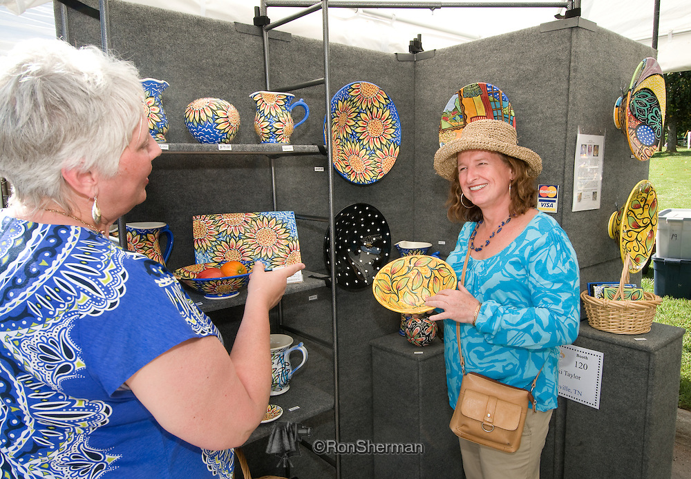 Rikki Taylor of Taylor Pottery shows prospect one of her plates at the Dunwoody GA Art Festival May 2010.