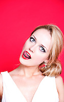 Caucasian woman wearing white dress on red background licking her lips