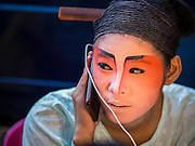 18 JANUARY 2015 - BANGKOK, THAILAND:  A performer with the Sai Yong Hong Opera Troupe talks on her smart phone before performing at the Chaomae Thapthim Shrine, a Chinese shrine in a working class neighborhood of Bangkok near the Chulalongkorn University campus. The troupe's nine night performance at the shrine is an annual tradition and is the start of the Lunar New Year celebrations in the neighborhood. The performance is the shrine's way of thanking the Gods for making the year that is ending a successful one. Lunar New Year, also called Chinese New Year, is officially February 19 this year. Teochew opera is a form of Chinese opera that is popular in Thailand and Malaysia.             PHOTO BY JACK KURTZ