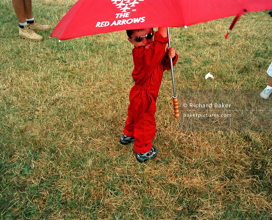 Young lad wears merchandising flight suit of the 'Red Arrows', Britain's Royal Air Force aerobatic team at air show.