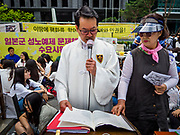 "SEOUL, SOUTH KOREA: A Catholic priest leads prayers during the Wednesday protest in front of the Japanese embassy in Seoul. The Wednesday protests have been taking place since January 1992. Protesters want the Japanese government to apologize for the forced sexual enslavement of up to 400,000 Asian women during World War II. The women, euphemistically called ""Comfort Women"" were drawn from territories Japan conquered during the war and many came from Korea, which was a Japanese colony in the years before and during the war. The ""comfort women"" issue is still a source of anger of many people in northeast Asian areas like South Korea, Manchuria and some parts of China.       PHOTO BY JACK KURTZ   <br /> Wednesday Demonstration demanding Japan to redress the Comfort Women problems"