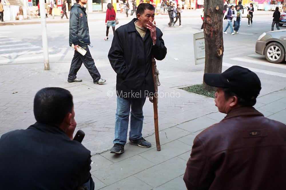 "Yi Bai Quan, a ""bang bang man"", waits for work in Chongqing, China. Yi Bai Quan, 53, is a ""bang-bang man"" in Chongqing. ""Bang Bang men"" act as porters carrying goods all around Chongqing city. Photographer: Markel Redondo."