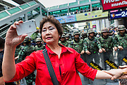 "25 MAY 2014 - BANGKOK, THAILAND: A Thai ""Red Shirt"" supporter of the ousted civilian government takes a ""selfie"" of herself in front of soldiers at a demonstration against the military junta. Public opposition to the military coup in Thailand grew Sunday with thousands of protestors gathering at locations throughout Bangkok to call for a return of civilian rule and end to the military junta.     PHOTO BY JACK KURTZ"
