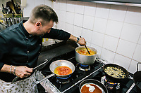 "NAPLES, ITALY - 10 OCTOBER 2018: Chef Potito Izzo cooks at La Taverna a Santa Chiara, a tavern in the historical center of Naples, Italy, on October 10th 2018.<br /> <br /> The idea of the founders Nives Monda and Potito Izzo (two really unusual names in southern Italy) was to create a ""taste gate"" of Campania products. La Taverna a Santa Chiara, founded in 2013, is a modern tavern whose strengths are the choice of regional and seasonal products and mostly small producers. Small restaurant, small producers.<br /> The two partners tried to put producers and consumers in direct contact, skipping the distribution, and managing to reduce the costs of the products considerably. Nives and Potito managed to create a simple kitchen, at moderate costs but with high quality raw materials.<br /> ""A different restaurant idea,"" says Nives, ""the producers deliver their products at low prices and the tavern manages to make traditional dishes with niche products"".<br /> Nives Monda has been a labor consultant for 20 years. Potito Izzo is the chef who has always been loyal to the  family cuisine. When he embraced the idea of Nives he found in the tavern the natural place to express the tradition of Neapolitan cuisine. Nives defines him as a ""comfort food chef"". Their partnership is a true friendship that has lasted for over 10 years."