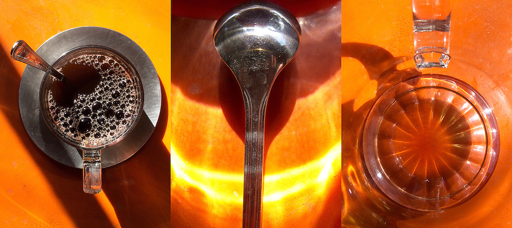 Triptych of a glass coffee mug on a pewter saucer, a coffee spoon, and the inside of a glass coffee mug.   resting on   The three were shot on an orange table in strong sunlight and shadows in a cafe in the West Village of Manhattan in the early morning.