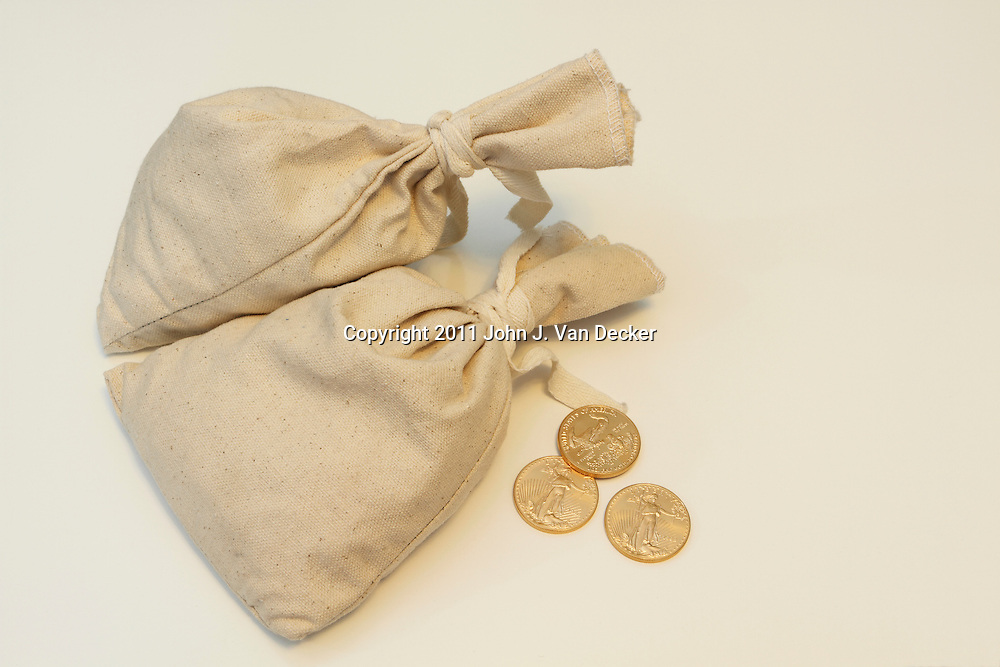 Two money bags with three 1 oz American Eagle gold coins